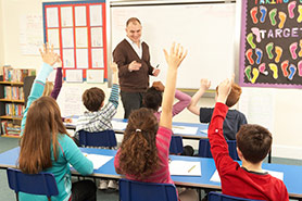 Children with Raised Hands in Class